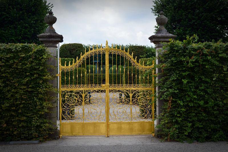 portail en fer forgé doré dans un jardin